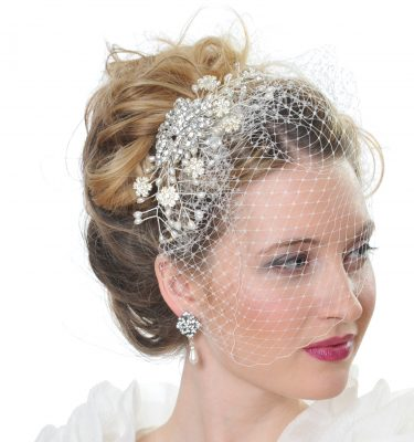 A pearl and crystal headpiece with birdcage veiling