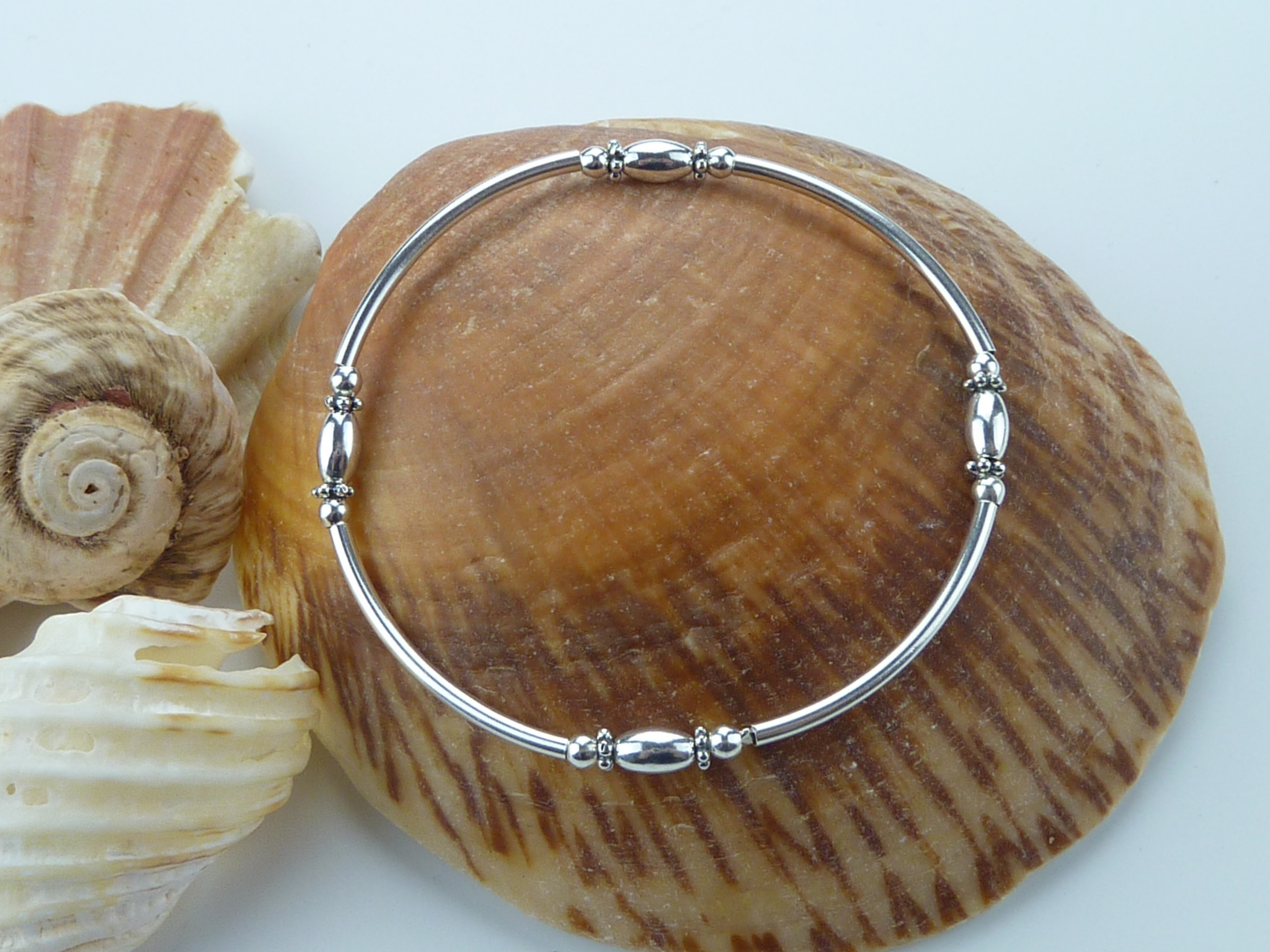 Sterling silver bar bracelet on a seashell