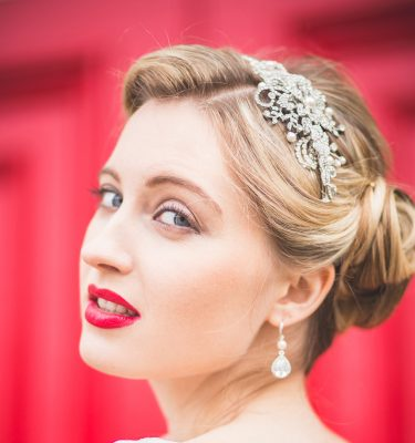 A diamante side headband on a bride with red background