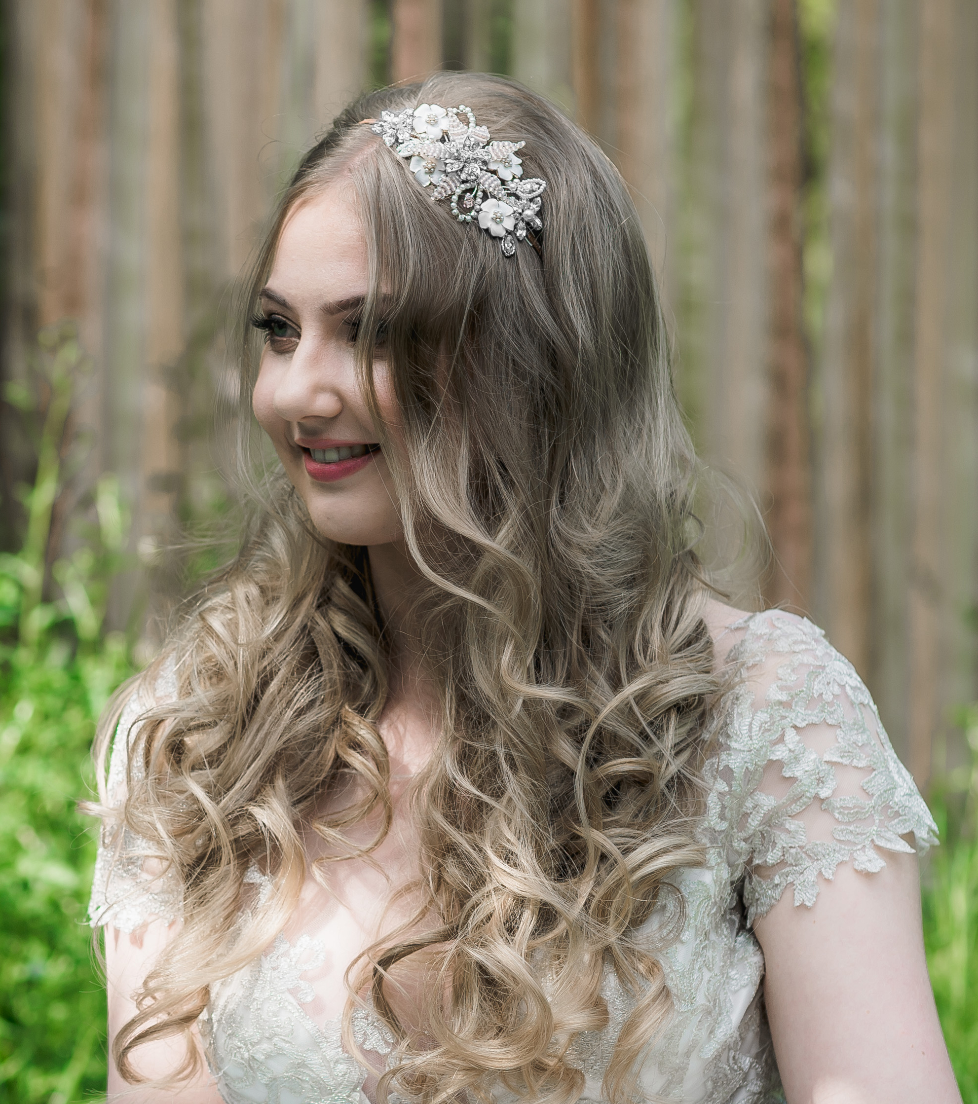 Bridal headpiece with ivory enamel flowers and blush beaded flower on a bride with long hair