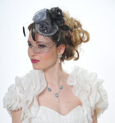 A wedding headpiece with black and grey roses