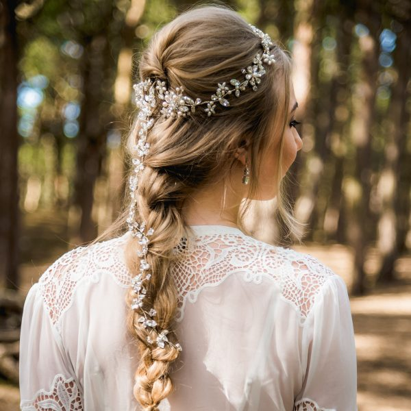 Bride in the woods wearing a long hairvine in a plait