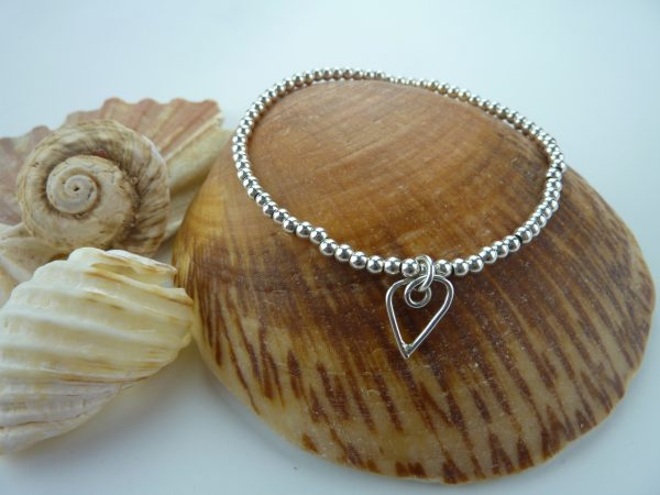 Sterling silver bead bracelet with heart charm on a seashell